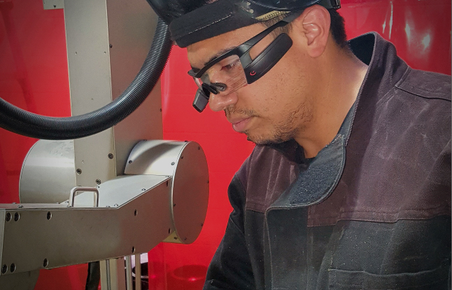 Welder wearing head up welding glasses while working with an automatic pipe welding machine